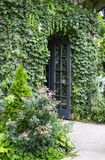 Vine covered building with flowers and wild roses and open french door - selective focus. A Vine covered building with flowers and wild roses and open french stock photos
