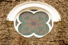 Vine covered church wall with rose window. The wall of this victorian-era church is covered by vines and shows a fine example of a rose window Stock Photography