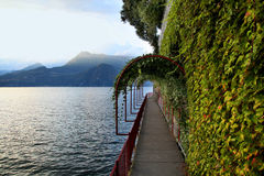 Vine covered walkway along Lake Como in Varenna Italy. Charming vine covered path along the shore of Lake Como in Varenna Italy royalty free stock photography