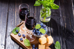 Vine and food. Two glass with red vine,cheese,blueberry and mint Royalty Free Stock Photos