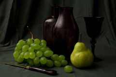 Vine and grapes on vintage tablecloth. Sophisticated flemish style still life with pear, grapes, decanter and gold knife Stock Image