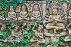 Vine growing on buddha statue wall Stock Photo