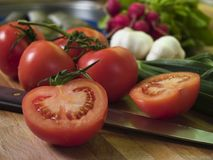Vine Tomatoes. And knife at cutting board, vegetables at background Stock Photography