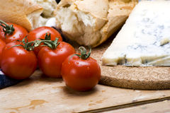 Vine tomatoes and blue cheese. A delicious spread of vine tomatoes, french bread and cheese on wooden table Stock Photography