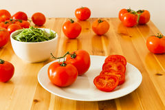 Vine Tomatoes And A Bowl Of Rocket Leaves Stock Photo