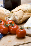 Vine tomatoes and french loaf. A delicious spread of vine tomatoes, french bread and cheese on wooden table Stock Photos