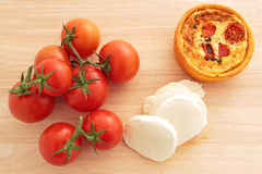 Vine tomatoes, mozzarella, and a tomato and mozzarella tartlet. Vine tomatoes, sliced mozzarella, and a tomato and mozzarella tartlet on a wooden board Stock Photography
