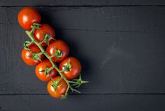 Vine tomatoes on rustic black wooden table - Top view photo royalty free stock photography