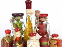 Vinegar Bottle Tops. A colorful assortment of pickled spices in different shaped jars on white Stock Photo