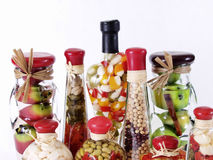 Vinegar Bottles. A colorful assortment of pickled spices in different shaped jars on white Stock Images
