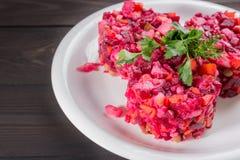 Vinegret schließen oben - traditioneller russischer Salat und Gemüse der roten Rübe mit Kräutern auf weißer Platte und Holztisch lizenzfreie stockbilder