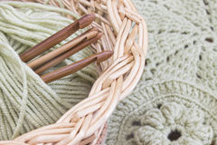 Vines basket with handmade crochet doilies, coasters and hooks. Cotton yarn for knitting. Work place. Stock Photo