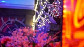 Vinexponeringsglas exponerade med röda och blåa ljus hänger ovanför stångräknare arkivfilmer