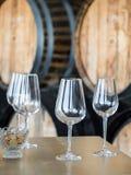 Vinexponeringsglas framme av trävinfat royaltyfri foto