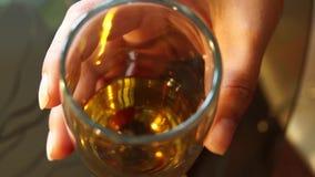 Vinexponeringsglas i en flickahand stock video