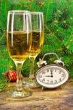 Vinexponeringsglas, klockor, julleksaker, nära träd för nytt år. Royaltyfria Bilder