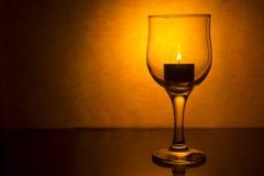 Vinexponeringsglas med en stearinljus Arkivfoto