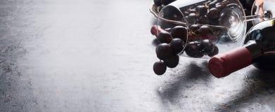 Vinexponeringsglas med klungor för röd druva, flaska av vin på mörk bakgrund, baner eller mall ställe för din design arkivbilder