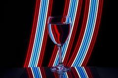 Vinexponeringsglas med neonljus bakom arkivfoto