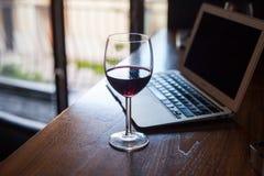 Vinexponeringsglas med rött vin- och bärbar datordatoren. Royaltyfri Foto