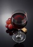 Vinexponeringsglas och druvor på svart Arkivfoto
