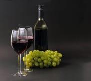 Vinexponeringsglas och flaska med druvor Royaltyfria Bilder