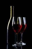 Vinexponeringsglas och flaska med rött vin som isoleras på svart Arkivfoto