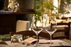 Vinexponeringsglas och tabellinbrottrestaurang Arkivbilder