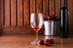 Vinexponeringsglas och vinflaska med röda druvor på träbakgrund fotografering för bildbyråer