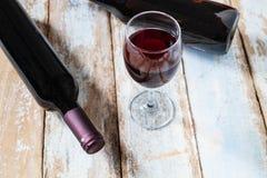 Vinexponeringsglas och vinflaska på gammal Wood bakgrund arkivbilder