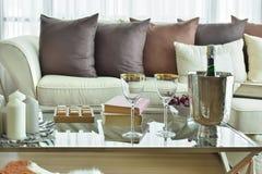Vinexponeringsglas och vinflaska på tabellen med den beigea soffan med kuddar för mörk brunt Fotografering för Bildbyråer