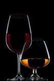 Vinexponeringsglas och whiskyexponeringsglas på svart bakgrund Arkivbilder