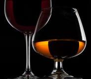 Vinexponeringsglas och whiskyexponeringsglas på svart bakgrund Royaltyfri Foto