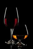 Vinexponeringsglas och whiskyexponeringsglas på svart bakgrund Royaltyfri Fotografi