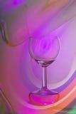 Vinexponeringsglas på en abstrakt kulör bakgrund arkivfoto
