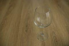 Vinexponeringsglas på en trätabell Fotografering för Bildbyråer