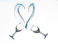Vinexponeringsglas som gör hjärta att forma färgstänk royaltyfri foto