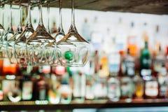 Vinexponeringsglas som hänger från metall, strålar på defocused bakgrund S royaltyfri bild