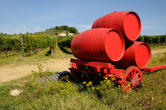Vineyard in Chianti and old red wagon with wine barrels, Tuscany region. Vneyard in Chianti in Tuscany, Italy Royalty Free Stock Image