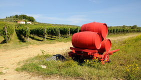 Vineyard in Chianti and old red wagon with wine barrels, Tuscany region. Vneyard in Chianti in Tuscany, Italy Royalty Free Stock Photos