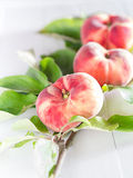 Vineyard peaches with sheets. On a white tray stock image
