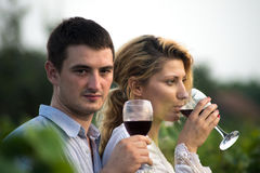 Vineyard. Young happy couple holding a glass of wine and looking at camera in the grape fields Stock Photo