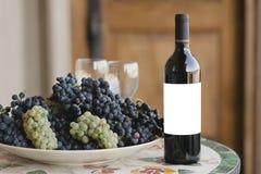 Vinflaska med den tomma etiketten bredvid druvor och vinexponeringsglas arkivbilder