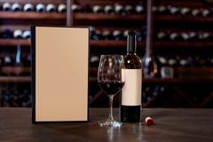 Vinflaska med exponeringsglas och meny på tabellen Arkivbild