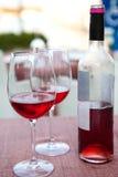 Vinflaska med två exponeringsglas av rosa vin Arkivbilder