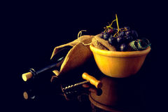 Vinflaska och druvor som isoleras på mörk bakgrund arkivbild