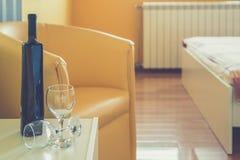 Vinflaska och två exponeringsglas i sovrum arkivbilder