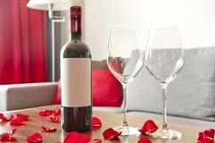 Vinflaska, två exponeringsglas och rosa kronblad på en tabell - romantiker a Arkivfoto