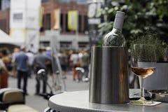Vinflaskan i kylare med ett exponeringsglas steg Royaltyfri Foto