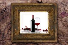 Vinflaskan med exponeringsglas och gruppen av röda druvor på gammal klassisk träram sned vid handen på wood bakgrund Arkivbild